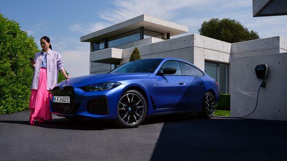BMW i4 M50 G26 2021 BMW Individual Frozen Portimao Blau metallic Dreiviertel-Seitenansicht mit Frau vor Haus